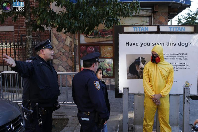 Ufficiali 3NYPD chiedono un uomo che indossa dispositivi di protezione individuale come un costume di Halloween, di allontanarsi dalla zona vicino all'edificio dove il dottor Craig Spencer vive a New York. EDUARDO MUNOZ / REUTERS